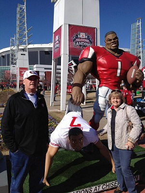 Parents of 49ers QB, Colin Kaepernick, pose with Chisel 3D sculpted statue of Falcons football player giving wedgie to a replica of Kaepernick